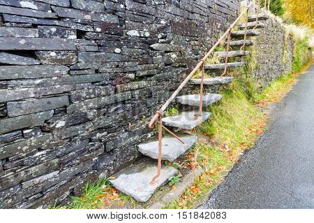Set of cantilevered steps made of slate ascending wall.
