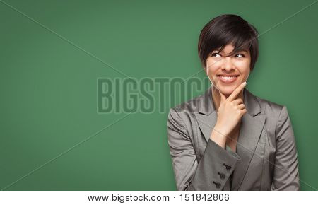 Attractive Young Mixed Race Woman Looking Up to Blank Chalk Board.