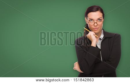 Serious Young Woman with Pencil and Glasses In Front of Blank Chalk Board.