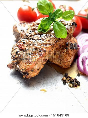 juicy steak, basil and tomatoes on a light background