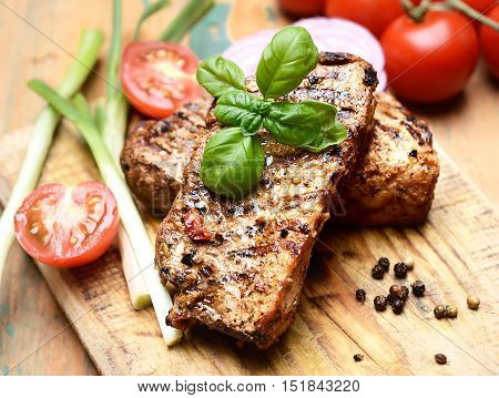 juicy steak, basil and tomatoes on a wooden background