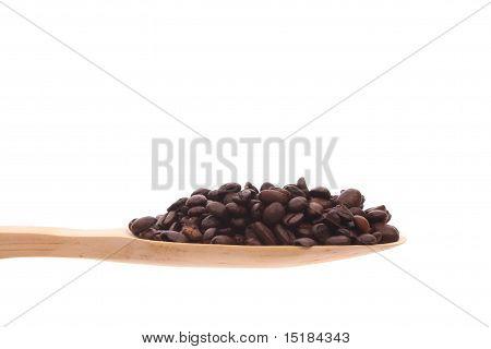 Kaffeebohnen auf einem Holzlöffel isoliert auf weißem Hintergrund