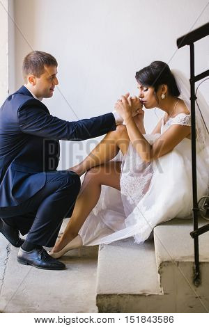 Beautiful bride woman kisses gold wedding ring on hand of groom man standing on knee over white wall