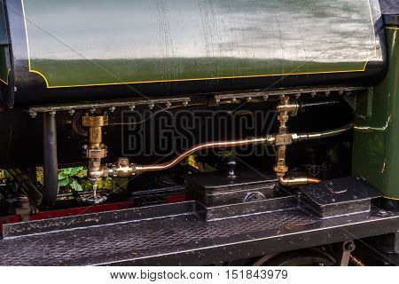 Close up of brass pipes on outside of steam locomotive.