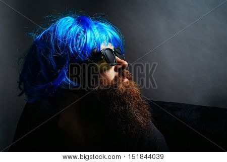 Handsome man hipster fashion model with long brunette beard with moustache in sunglasses and blue wig on grey background
