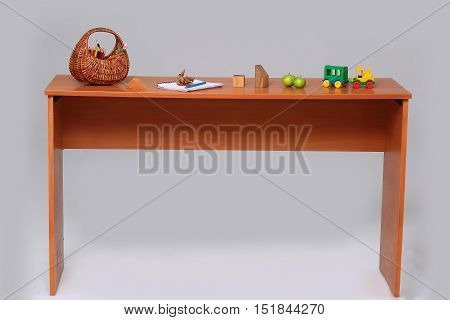 School desk with wicker basket full of colorful colored pencils green apples car toy wooden cubes paper notebook on gray background studio