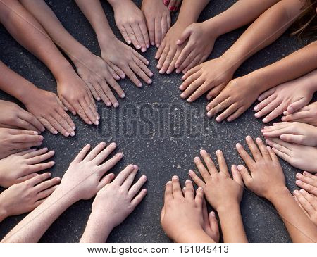 The hands of several children are together on a paved playground.  Shot from above.