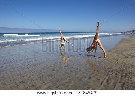 Teenage Girls at the Beach.  They are doing cartwheels in the wet sand.