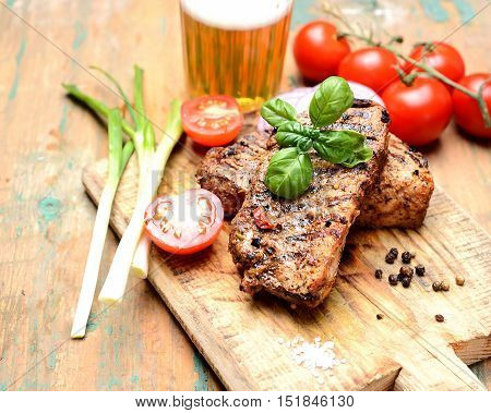 juicy steak, basil, beer and tomatoes on a wooden background
