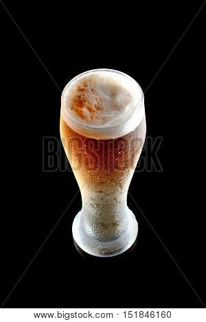 Fresh beer in a glass on a black background. The concept of food.