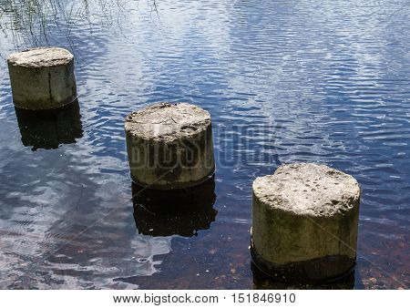 three concrete pillars by the river side