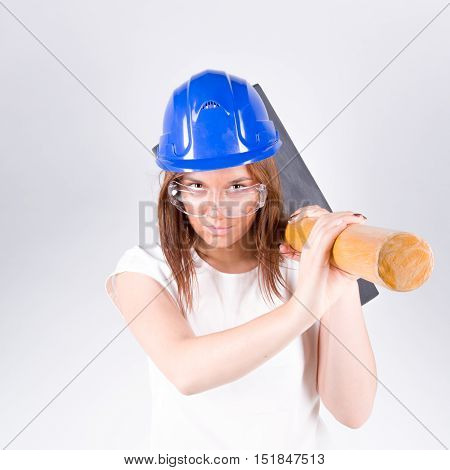 Girl in a blue helmet with a sledgehammer