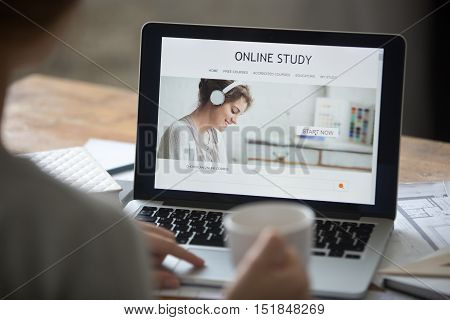 Open laptop on the desk with a title online study on the screen. Education concept photo, view over the shoulder, close-up