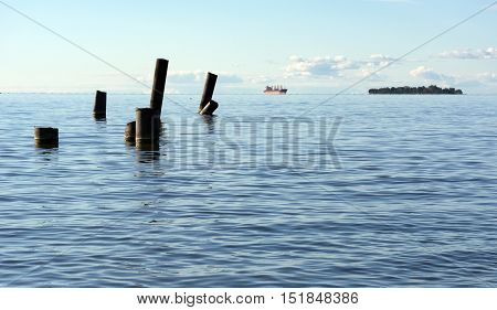 The Gulf of Finland with blue water sea on the horizon sailing ship ship sticking out of the water pipe stick blue sky Russia