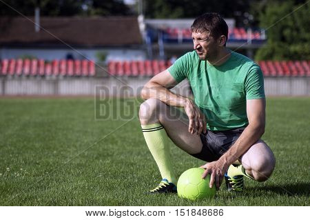 Football player with ball on green sport field.