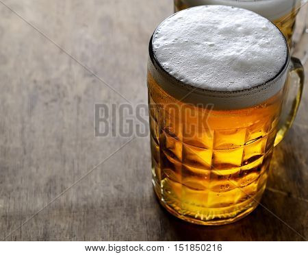 cold beer in a mug on the wooden background