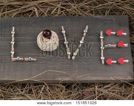 Word love writing with clothes pin red and silver hearts and cherry on wooden board on hay background
