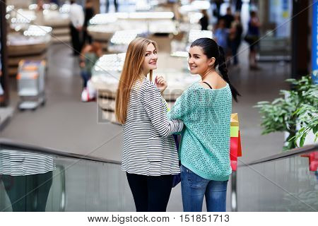 Women with bags on the moving staircase