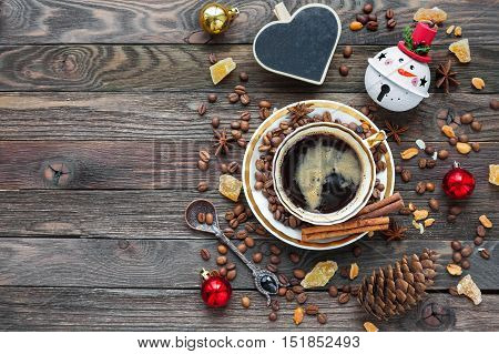 Rustic wooden background with cup of coffee and New Year decorations. Christmas beverage with heart chalkboard. Top view place for text.
