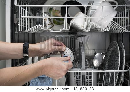 Male hands with cloth cleaning a dish ware inside the open dish washer indoors cropped closeup