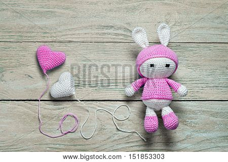 Crochet Bunny Toy On A Wooden Background With Balloons In The Form Of Hearts On Wooden Background, T