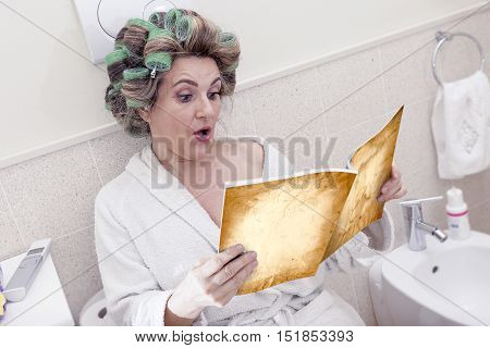 Beautiful Lady Sitting On The Toilet Reading A Magazine