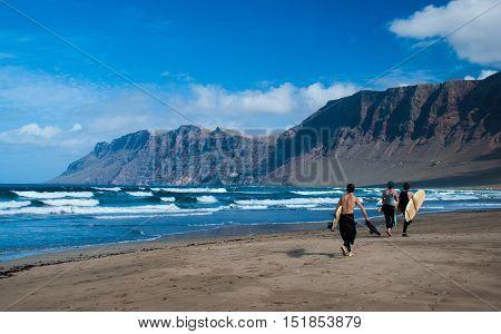 Surfers in the northern shore of Lanzarote Island, Famara