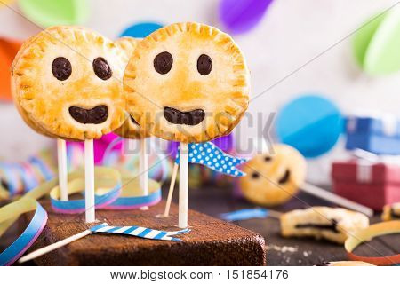 Homemade shortbread smiley cookies with dark chocolate on stick called pie pops. Childrens party background.