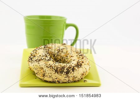 Bagel and coffee presentation with garlic sesame and poppy seeds as topping and green mug adjacent. Still life in horizontal image with copy space. Crumbs on plate.