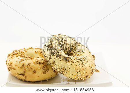 Everything bagel propped against onion bagel on white plate. Specialty toppings are sesame and poppy seeds roasted onion and garlic bits. Horizontal image with copy space.