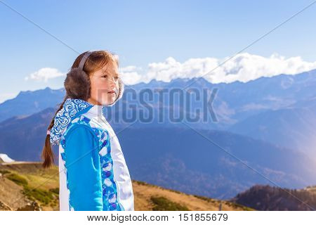 Girl with pigtail dressed in jacket and warm fluffy headphones admires of autumn mountain landscape views of hills and peaks of Caucasus mountains. Krasnaya Polyana Alpine ski resort. Sochi Russia