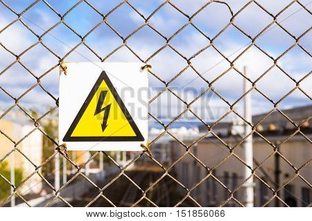 Yellow warning sign with high voltage symbol hanging on the protective metal grid. Protection on high voltage train wires. Transport infrastructure of Russian Railways Saint-Petersburg