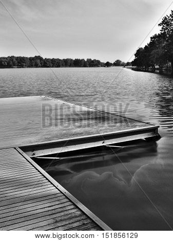 black and white photo of wooden pier on Alum Lake 'Kamencove jezero' in Chomutov city at the end of the summer tourist season