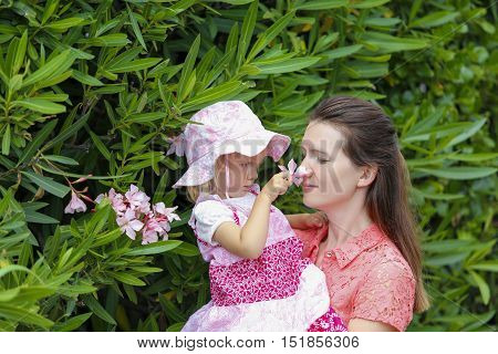 Cute daughter present her mother the pink flower and happy mother smelling it with enjoying face on green summer background