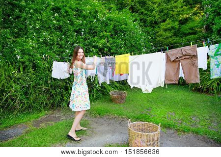 Smiling Young Woman Hanging Laundry On Clothesline At The Backyard