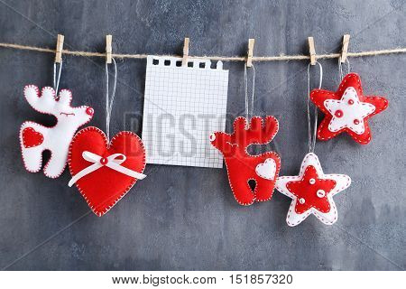 Christmas Decorations Hanging With Blank Sheet Of Paper On Rope On Grey Background