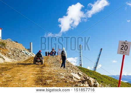 Sochi Russia - October 31 2015: Sports mountain ATV Quad Bike with passengers coming up the mountain. Hills and peaks of Caucasus mountains. Krasnaya Polyana - Alpine ski resort constructed for Sochi games. Rosa Khutor Sochi Russia