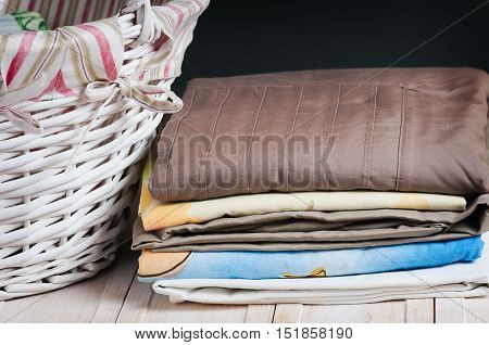 bedclothes different colors in wicker basket on light background