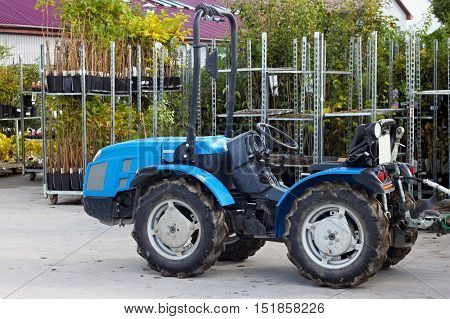 Small tractor in the backyard of nursery for ornamental plants.