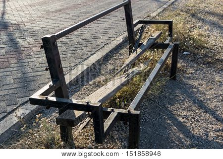Old broken wooden bench with iron frame
