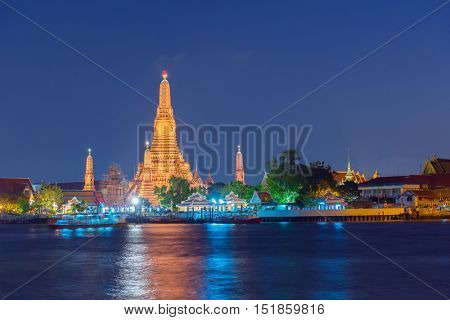 Large illuminated temple Wat Arun after sunset seen accross river Chao Phraya. Bangkok, Thailand