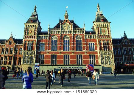 AMSTERDAM, NETHERLANDS - MAY 3, 2016: People near the Amsterdam Central Train Station(Centraal) in Amsterdam, Netherlands. Central Station is the central railway station of Amsterdam and is used by 250000 passengers a day. sunset light