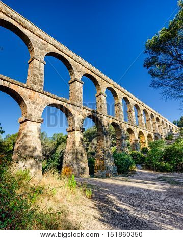 Roman aqueduct in morning sunlight near Tarragona, summer Spain