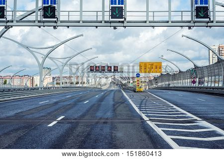 Wide highway with road signs and information banner over traffic lanes. Highway ring road around the big city
