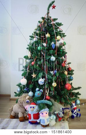 Knitted toys Father Frost, Snow Maiden and animals under christmas tree