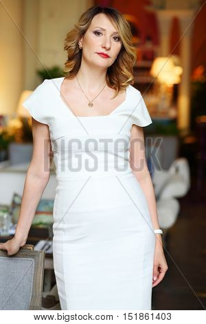 Beautiful middleaged woman in white dress poses in restaurant, shallow dof