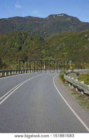 Carretera Austral road in the Aysen Region of southern Chile passing through forested mountains in the area of Lag Yelcho.