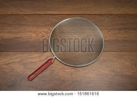Metallic strainer with plastic handle on wooden background - a modern kitchen utensil.