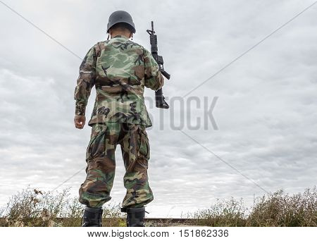 horizontal image of soldier standing at the top of  a hill with his back turned holding up his gun and looking up at the cold grey sky with a strip of dead grass at the bottom of the image .