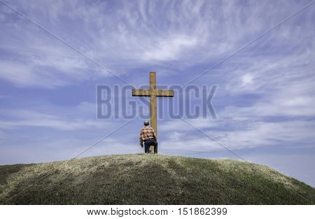 horizontal image of a man kneeling by a wooden cross on a grassy hill surrounded by a beautiful blue sky with wispy white clouds floating by in the summer time.